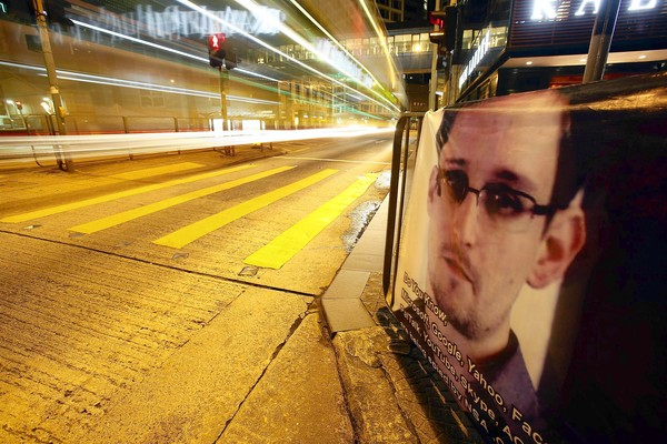 A bus passes by a poster of Edward Snowden, a former contractor at the NSA displayed by his supporters at Hong Kong's financial Central district